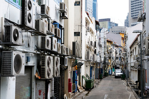 These are heat exchangers of air-conditioning units in Singapore. As urban temperatures rise, so does our discomfort and, therefore, our use of air-conditioning. This not only increases release of GHGs, but also generates heat, further exacerbating the UHI. Photo: Peter Morgan. Own work – Creative Commons. http://creativecommons.org/licenses/by-nc-nd/4.0/